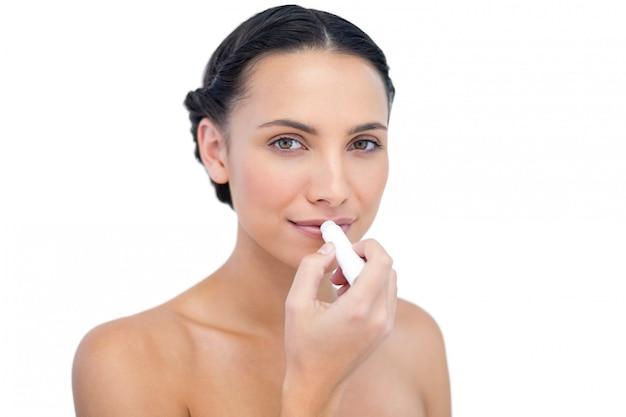 Modelo natural jovem sensual, aplicar protetor labial