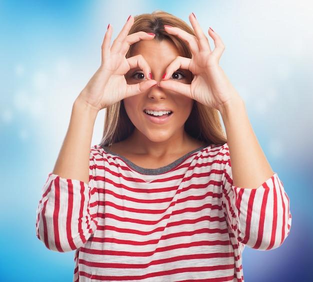 Modelo olhando através de binóculos mão