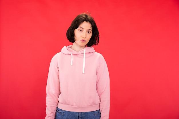 Modelo pensativo com capuz rosa olhando para frente no estúdio vermelho