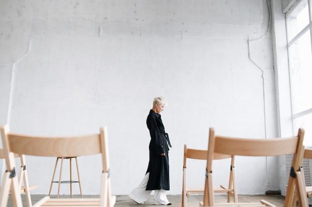 Modelo pensativo em casaco preto caminha entre as cadeiras em um estúdio
