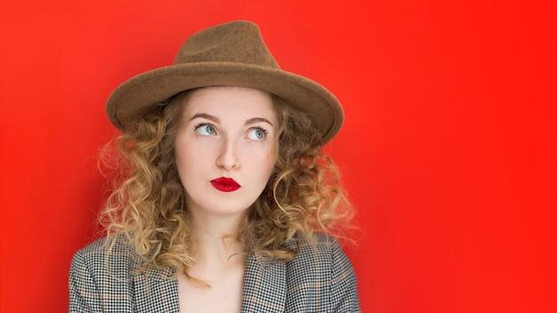 Modelo pensativo em estúdio, olhando para longe. jovem mulher engraçada de olhos verdes com chapéu pensando sobre fundo vermelho. emoções faciais expressivas