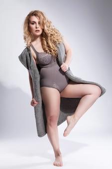 Modelo plus size vestindo lingerie e cardigã cinza