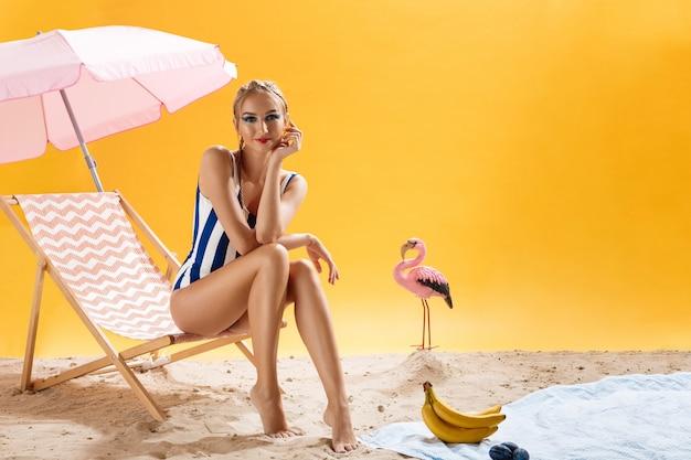 Modelo posa com a mão no rosto, sentado na decoração de verão