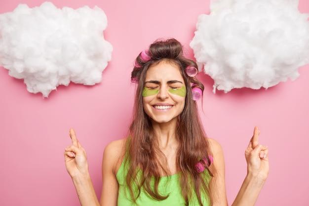 Modelo positivo feminino de cabelos escuros sorri docemente, usa rolos de cabelo e esponjas sob os olhos cruza os dedos faz desejos, esperanças, sonhos, torna-se realidade poses em roupas casuais isoladas sobre uma parede rosada