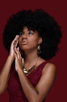 Modelo preta com cabelo afro grande exibe brincos grandes e colar dourado com vestido vermelho