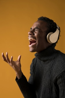 Modelo preto cantando com fones de ouvido