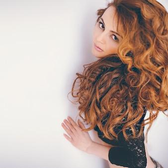 Modelo ruiva sensual com longos cabelos cacheados