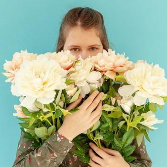 Modelo segurando buquê de flores plano médio