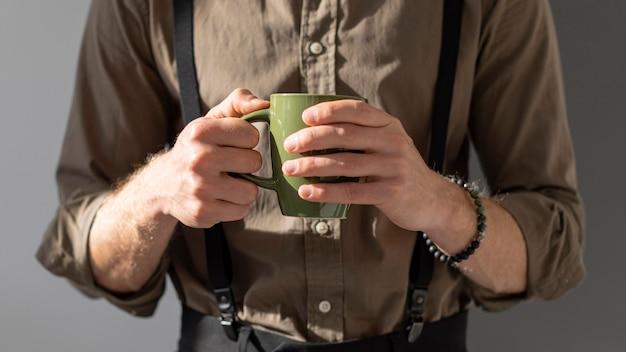 Modelo segurando uma xícara de café com as duas mãos