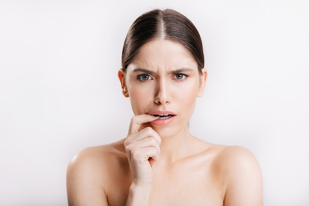 Modelo sem maquiagem posando na parede branca. retrato de mulher descontente, mordendo o dedo de dúvida.