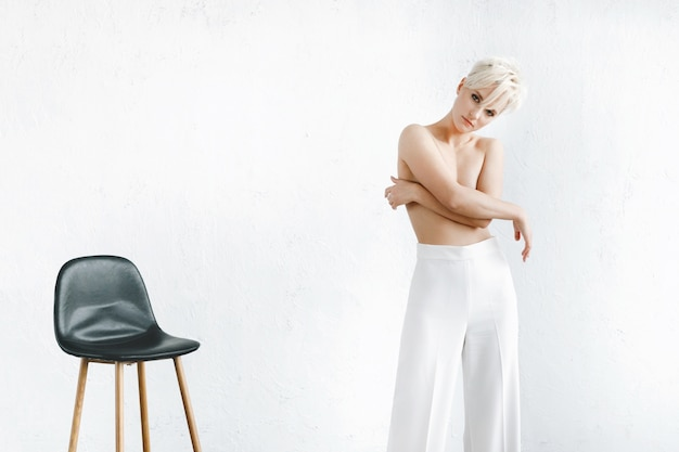 Modelo semi-nua em calça branca está diante de uma parede branca no estúdio
