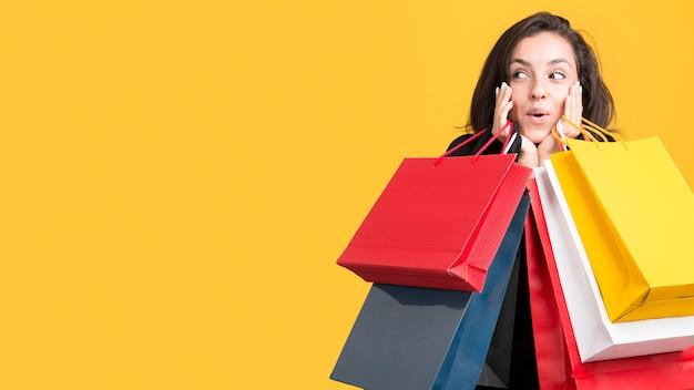Modelo sendo coberto por sacolas de compras copie o espaço