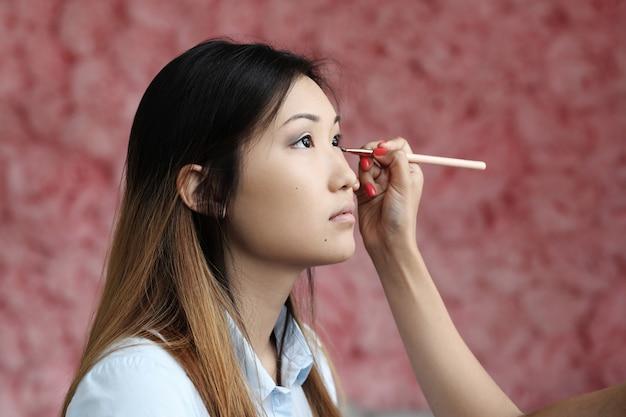 Modelo sendo maquiagem por profissionais