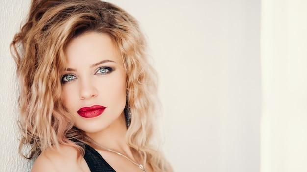 Modelo sensual com cabelos loiros ondulados e lábios vermelhos olhando