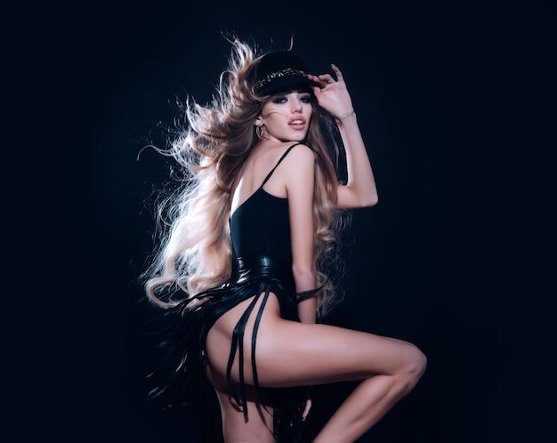 Modelo sexy com cabelo comprido e ventoso em pose de chapéu preto no estúdio. corpo magro de jovem em fundo preto.
