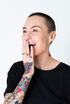 Modelo skinhead tatuado em camiseta preta rindo no estúdio