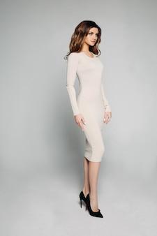Modelo slim com cabelos ondulados morena posando em vestido de marfim e salto preto.