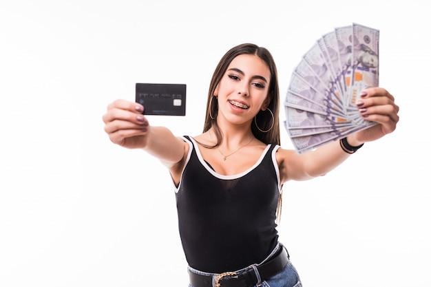 Modelo sorridente de camisa preta segura leque de notas de dólar e cartão de crédito