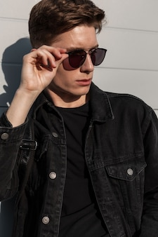 Modelo urbano americano coloca óculos de sol vintage na rua em dia de sol