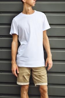 Modelo urbano de roupas. cara estiloso de pé perto da parede de metal cinza com uma camiseta em branco e shorts marrons. maquete pronta para você projetar.