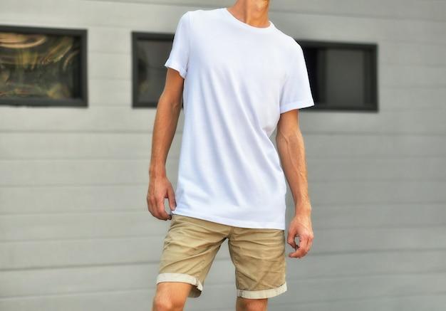 Modelo urbano de roupas. homem yong em uma camiseta em branco e shorts marrons está perto da parede texturizada branca com janelas pretas. o maquete pode usar para você projetar.