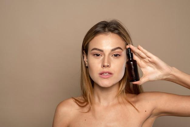 Modelo usando produto cosmético natural para derma facial hidratado, brilhante e saudável. óleo essencial para terapia anti-envelhecimento.