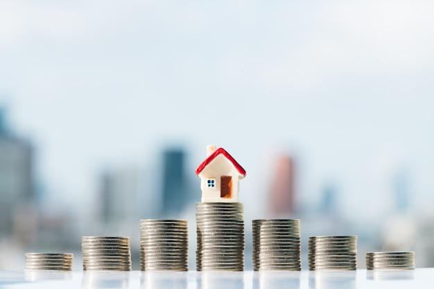 Modelo vermelho da casa sobre a pilha das moedas com fundos da cidade.