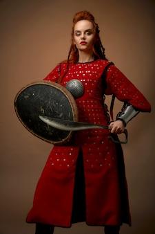 Modelo vestindo traje medieval, posando com punhal, escudo
