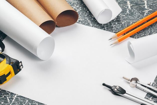 Modelos arquitetônicos e rolos de planta e um desenho de instrumentos na mesa de trabalho.