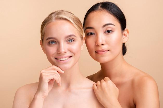 Modelos caucasianos e asiáticos de close-up posando juntos