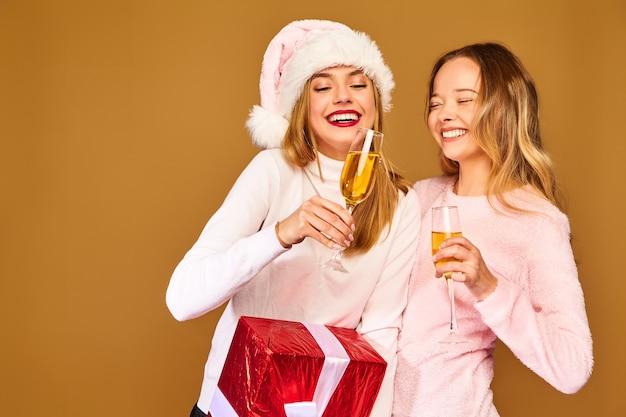 Modelos com grande caixa de presente bebendo champanhe em copos comemorando o ano novo