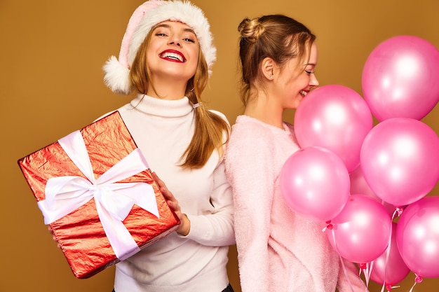 Modelos com grande caixa de presente e balões rosa no natal