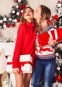 Modelos com suéteres quentes sentados perto da árvore de natal decorada na véspera de ano novo.