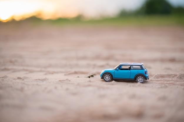 Modelos de brinquedos de carro estão na estrada com fundo desfocado de luz solar