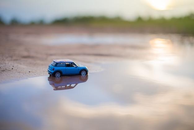 Modelos de brinquedos de carro estão no reflexo da água com fundo desfocado de luz solar