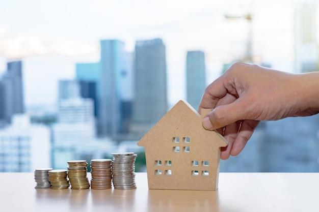 Modelos de casa de madeira e mão segurando moedas dispostas em linhas no fundo do edifício
