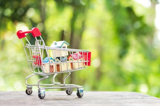 Modelos de casa empilhamento no carrinho de compras. conceito de escada de propriedade