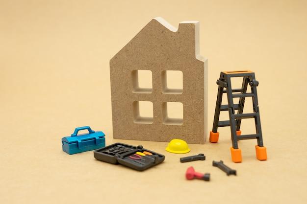 Modelos de casas e modelos de equipamentos existem modelos de capacetes de construção amarelos.