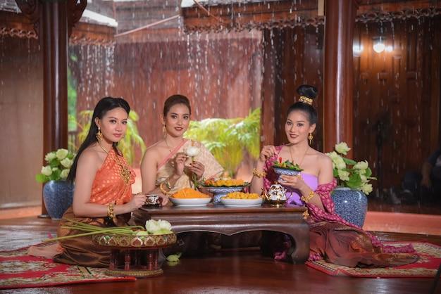 Modelos de estilo de vida de mulheres tailandesas usam vestidos tradicionais tailandeses em belas casas tailandesas em ayutthaya, tailândia.