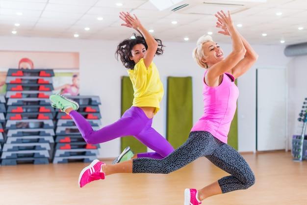 Modelos de fitness exercitando na academia, dançando zumba.