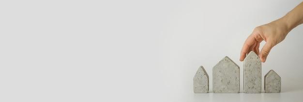 Modelos de mini casa e mão no fundo branco. compre uma casa. conceito de escada de propriedade, hipoteca e investimento imobiliário. espaço livre para texto, cópia espaço, layout moderno, close-up.