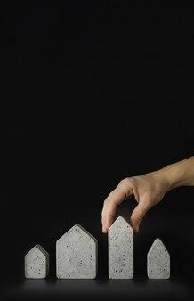 Modelos de mini casa e mão sobre o fundo preto. compre ou construa uma casa. conceito de escada de propriedade, hipoteca e investimento imobiliário. espaço livre para texto, cópia espaço, layout moderno, close-up.