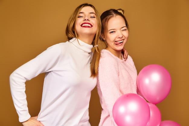 Modelos de mulheres com balões de ar rosa na parede dourada