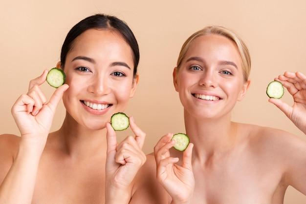 Modelos de smiley close-up posando com fatias de pepino