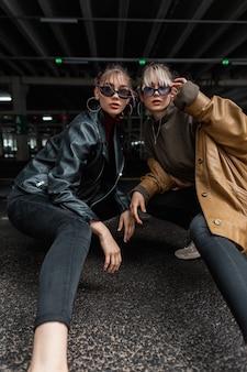 Modelos elegantes e elegantes de duas mulheres com jaqueta de couro elegante e blusa com jeans preto posando na cidade