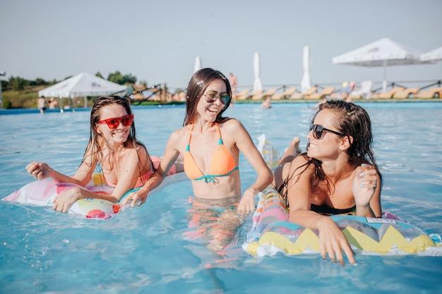 Modelos felizes estão na piscina. eles posam na câmera. dois modelos estão deitados em carros alegóricos e olham para a mulher no meio. ela fica na água e sorri.