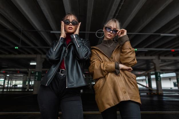 Modelos legais amigas amigas em óculos de sol da moda com jaqueta de couro estilosa e suéter posando em um estacionamento na cidade