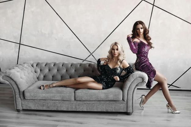Modelos lindos posando no sofá cinza.