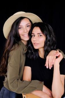 Modelos, meninas irmãs ou amigos morena, olhando para a câmera, sorrindo, se divertindo e abraçando.