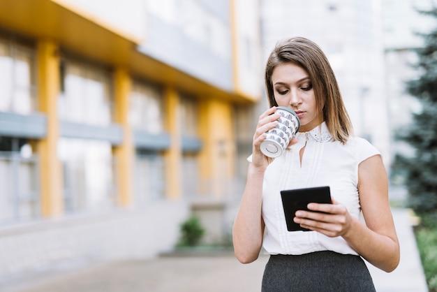 Modern jovem empresária bebendo café enquanto olha para smartphone